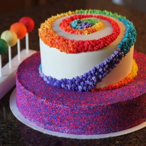 Rainbow swirl cake with bottom tier fully covered in sprinkles. Matching Rainbow Cake pops